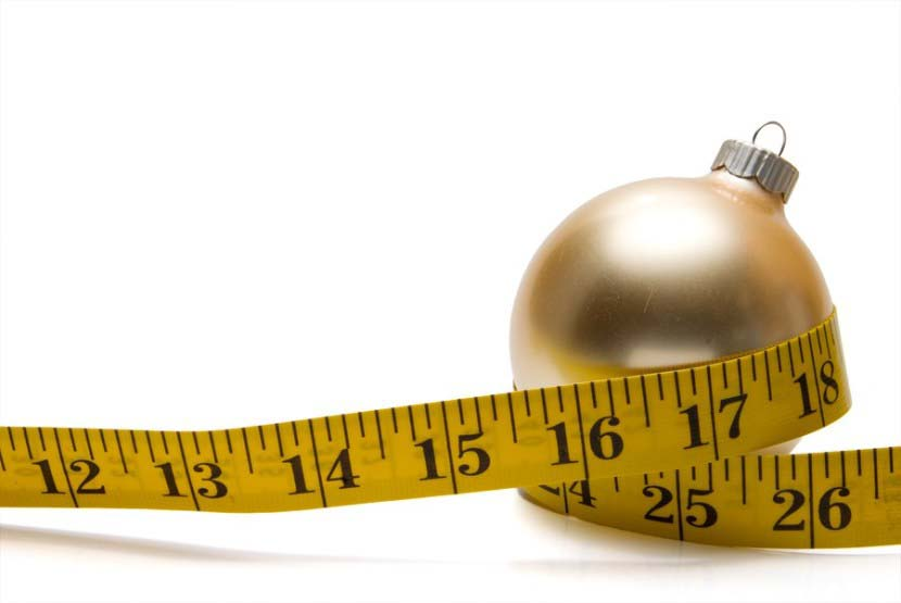 A Christmas ornament with measuring tape wrapped around it